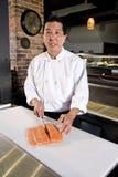 Chef japonais découpant les poissons crus pour des sushi photographie stock
