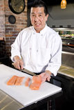 Chef japonais découpant les poissons crus pour des sushi Photographie stock libre de droits