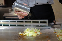 Chef japonais délibérément préparant et faisant cuire le teppanyaki traditionnel de boeuf photos libres de droits