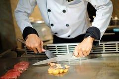 Chef japonais délibérément préparant et faisant cuire le teppanyaki traditionnel de boeuf photo libre de droits