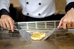 Chef japonais délibérément préparant et faisant cuire le teppanyaki traditionnel de boeuf images stock