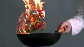 Chef jetant le wok en l'air flamboyant des poivrons banque de vidéos