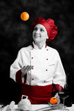 Chef juggling with orange Royalty Free Stock Images