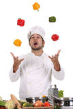 Chef juggling with peppers royalty free stock photography