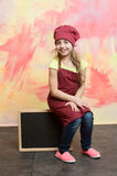Chef kid, happy girl cook in red chef hat, apron Stock Photos