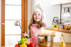 Chef kid preparing healthy food and showing thumb up Stock Photos