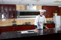 Chef in kitchen. Young male professional chef cleaning in commercial kitchen Royalty Free Stock Photography