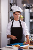 Chef in the kitchen. Female chef with headset giving a cooking demonstration to students Stock Image