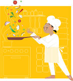 Chef in the kitchen. Chef fryies vegetables juggling them, kitchen in the backgroung Royalty Free Stock Photo