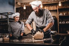 Chef kneading dough in the kitchen. Chef teaching his assistant to bake the bread in the bakery. Chef kneading dough in the kitchen. Chef teaching his assistant royalty free stock photography