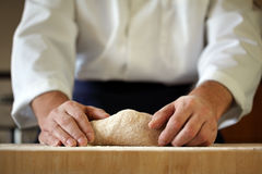 Chef kneading yeast dough. Making bread yeast dough, chef kneading in a bakery kitchen Royalty Free Stock Photography