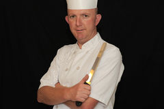 Chef and knife. Chef in white uniform holding knife with arms crossed Royalty Free Stock Photos