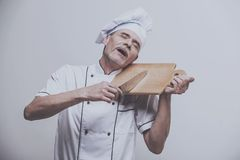 Chef with Knife Like Violinist. Isolated Grey Background. Cooking Concept. Happy White Man. Kitchen Uniform. Kitchenware Lifestyle. One Man Staff. Kitchen royalty free stock image