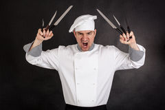Chef with knifes. Angry chef with knifes on black background Stock Image