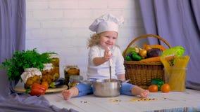 Chef, Kochmädchen, das gesundes Lebensmittel in der Wanne kocht stock footage