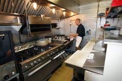 Chef-kok aan het werk in kleine keuken Stock Fotografie