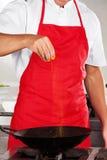 Chef-kok Adding Turmeric Powder in Pan stock afbeeldingen