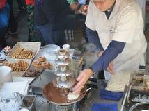 Chef-kok bij Chocoladefontein Stock Afbeeldingen