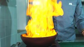 Chef-kok Cooking With Fire in Pan Professionele chef-kok in het commerciële keuken koken stock footage