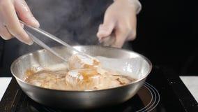 Chef-kok Cooking Het kooktoestel in handschoenen bereidt zeevruchten voor Kokende kammosselen in roomsaus in pan HD stock video