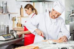 Chef-kok Cutting Ravioli Pasta met Collega het Zwaaien Stock Foto's