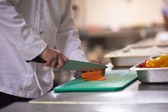Chef-kok in de plakgroenten van de hotelkeuken met mes Stock Afbeeldingen