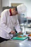 Chef-kok in de plakgroenten van de hotelkeuken met mes Stock Foto