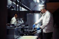 Chef-kok die aan de keuken werken stock foto