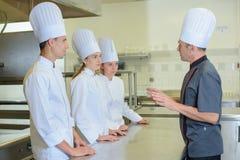 Chef-kok die aan stagiairs spreken royalty-vrije stock foto's