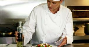 Chef-kok die afwerking op salade zetten stock videobeelden