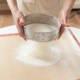 Chef-kok die bakpoeder ziften in deeg Royalty-vrije Stock Foto