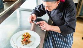 Chef-kok die beeld van voedsel maken dat hij met telefoon heeft gekookt stock foto's