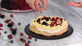 Chef-kok die bladerdeegcake met vla en besbessen, frambozen, braambessen, bosbessen maken Heerlijk Dessert stock videobeelden