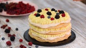 Chef-kok die bladerdeegcake met vla en besbessen, frambozen, braambessen, bosbessen maken Heerlijk Dessert stock footage