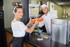 Chef-kok die burgers geven aan serveerster in commerciële keuken Stock Foto's