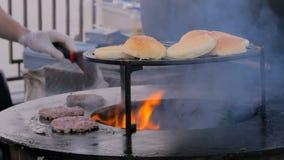 Chef-kok die burgers voorbereiden bij het festival van het straatvoedsel stock video