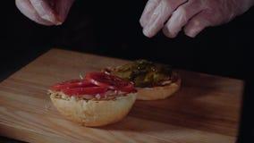 Chef-kok die de hamburger voorbereiden, die het broodje op de grill braden, die gesneden tomaten zetten stock videobeelden