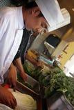 Chef-kok die in de keuken werkt Stock Afbeeldingen