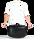 Chef-kok die een braadpan naar, over witte lijst houden royalty-vrije stock afbeeldingen