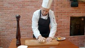 Chef-kok die een deeg kneden stock footage