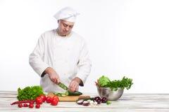 Chef-kok die een groene komkommer in zijn keuken snijden Stock Afbeeldingen