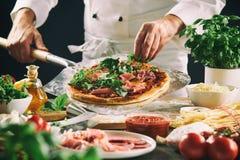 Chef-kok die een Italiaanse pizza op een peddel voorbereiden royalty-vrije stock foto