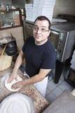 Chef-kok die een pizza maakt Stock Fotografie