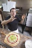 Chef-kok die een pizza maakt Royalty-vrije Stock Afbeeldingen
