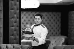 Chef-kok die een schotel voorstellen bij het hotelrestaurant, die een schotel met de zwart-witte tonen van een dekkingsdeksel sto stock afbeeldingen