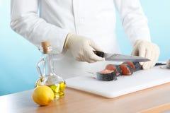 Chef-kok die een vis kookt stock foto's