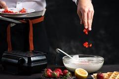 Chef-kok die fruit in wafelsdeeg toevoegen royalty-vrije stock foto