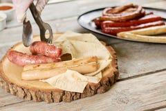 Chef-kok die geroosterde worsten op natuurlijk hout zetten Stock Foto