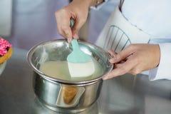 Chef-kok die glans voor desserts maken stock afbeeldingen