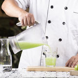 Chef-kok die Groen Apple gieten smoothie Stock Foto's